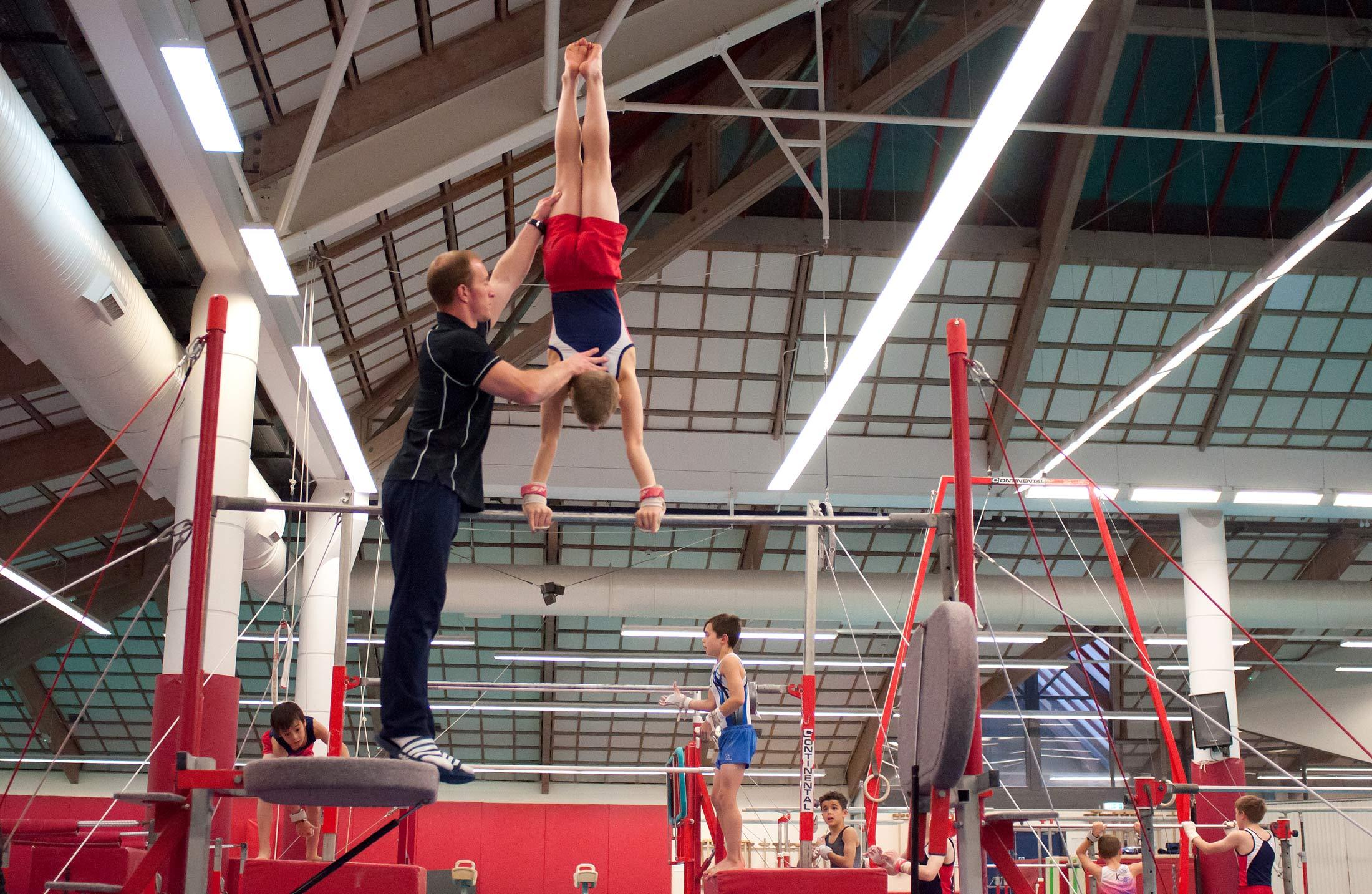 gymnast and coach handstand on high bar