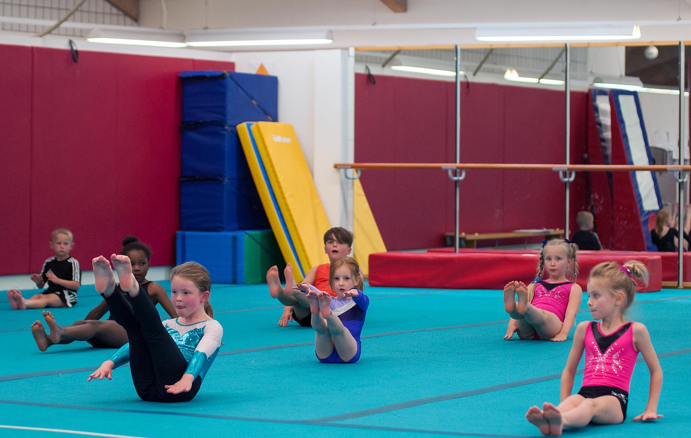 gymnasts in class raising legs