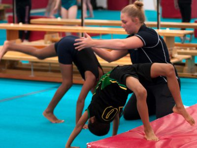 gymnasts being coached to handstand