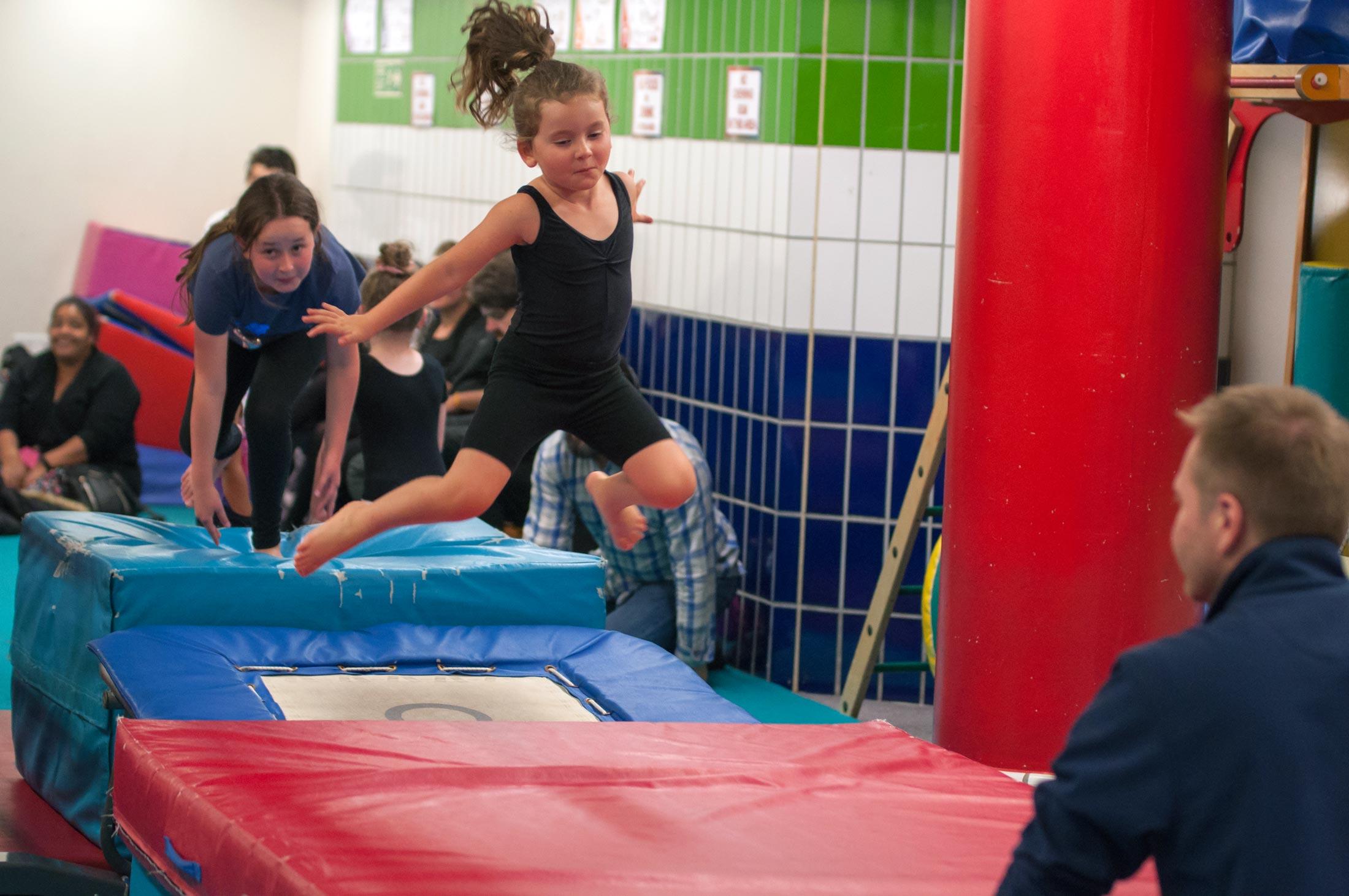 girl jumping off a trampette onto mats