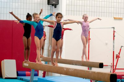 several young gymnasts practicing on beam