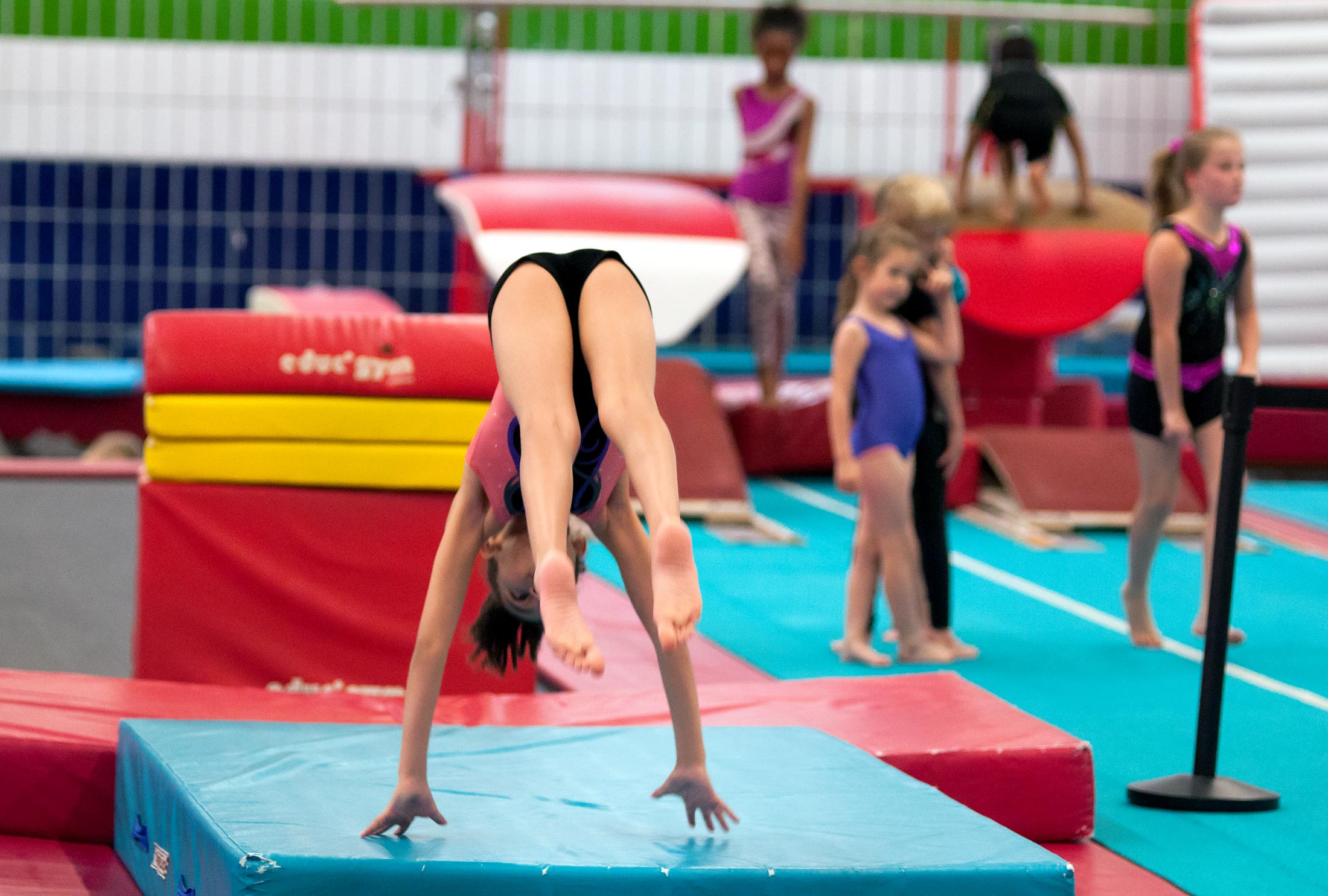 gymnast jumping into forward roll on mat