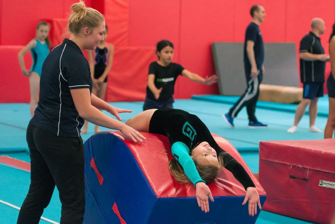 gymnast learning backward handspring