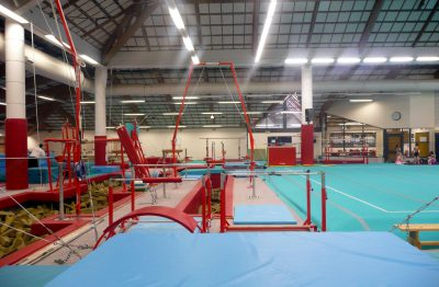 CMIG Main Gym Arena looking over crash mat to bars and floor apparatus